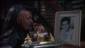 Why in the world does Macleod have his son's autographed headshot on his desk?